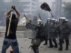 A protester prepares to hit riot police with a stick during clashes at Syntagma square, central Athens, Wednesday.