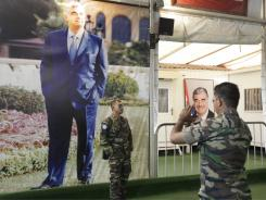 Malaysian UN peacekeeper soldiers take pictures next to a portrait of slain Lebanese Prime Minister Rafik Hariri, at his grave in downtown Beirut, Lebanon.