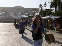 A woman covers her mouth to protect herself from lingering tear gas Thursday in Athens.