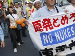 Demonstrators walk by the headquarters of Tokyo Electric Power Co. during an anti-nuclear power protest Thursday in Tokyo.