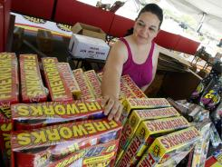 Dominique Tafoya arranges some of the new fireworks stock at a local fireworks concession stand  Friday in Phoenix.