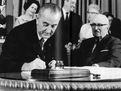 President Lyndon Johnson signs Medicare and Medicaid programs into law as former President Harry S. Truman looks on.