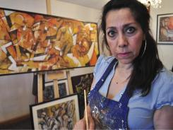Mexican artist Gilda Lorena Martinez poses next to one of her paintings in Ciudad Juarez, Mexico, on June 24.
