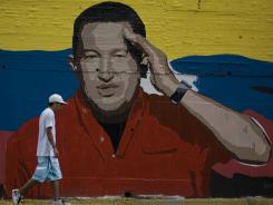 A man walks in front of a mural depicting Venezuela's President Hugo Chavez on Saturday in Caracas, Venezuela.