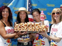 From left, women's championship contestants Larell Marie Mele, Juliet Lee, Sonya Thomas and Laura Leu pose together Friday after their official weigh-in for Nathan's Famous Fourth of July International Hot Dog Eating Contest, sponsored by Pepto-Bismol.
