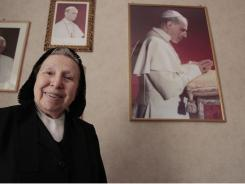 In this photo taken in Rome on  May 31, sister Margherita Marchione smiles near portraits of Pope Pius XII, right, Paul VI, center, and Pope Benedict XVI, left, during an interview with the Associated Press.