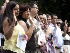 Ruth Salamanca of El Salvador, far left, takes the oath of citizenship Monday along with others during a ceremony at George Washington's Mount Vernon Estate and Gardens in Virginia.
