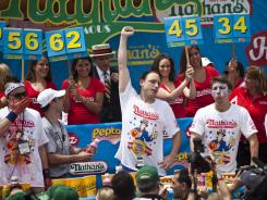 Joey Chestnut, center, celebrates winning at the end of the 2011 Nathan's Famous Fourth of July International Hot Dog Eating Contest at Coney Island.