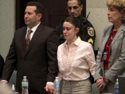 Casey Anthony holds hands with her defense attorneys, Jose Baez, left, and Dorothy Clay Sims, as Anthony was acquitted of murder at the Orange County Courthouse in Orlando on Tuesday.
