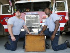 Firefighters Aaron Reilly, left, and Brandon Bailey kneel by a 116-pound chunk of I-beam at Rockledge Fire Department.