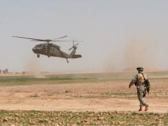 A U.S. helicopter lands in the field as a U.S. soldier stands guard near  Samarra, Iraq.