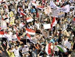 Syrian supporters of President Bashar Assad carry his pictures during a rally in the northern city of Aleppo.