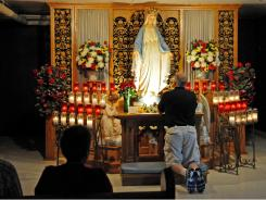 Visitors pray in the crypt at the Shrine of Our Lady of Good Help on June 30 in Champion, Wis.