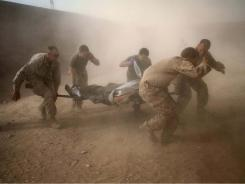 Marines deal with dust kicked up by a Black Hawk helicopter as they rush a colleague wounded from an improvised explosive device in Afghanistan's volatile Helmand province.
