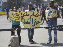 Protesters hold signs in  Martyrs Square in Suez, Egypt, on Tuesday after the court ordered the release of 10 policemen charged with killing protesters during the country's uprising.