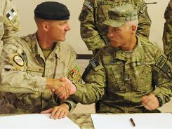 Dean Milner, commander of Canadian forces in Afghanistan, left, and U.S. Maj. Gen. James Terry  sign change in command papers during the handover ceremony at Kandahar airbase.