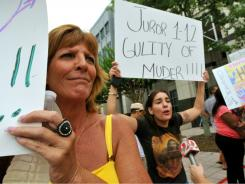 Linda Sigler, left, and Michelle Caballero protest Casey Anthony's acquittal outside of the Orange County Courthouse on Thursday in Orlando.