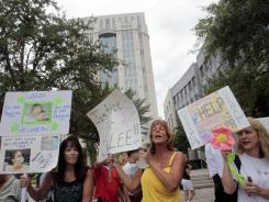 People dissatisfied with the the Casey Anthony verdict protest outside the Orange County Courthouse in Orlando on Thursday.