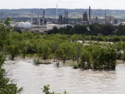 The Yellowstone River flows past the Exxon Mobil refinery in Billings, Mont., Wednesday. An Exxon Mobil pipeline near Laurel ruptured and spilled an estimated 1,000 barrels of crude into the Yellowstone.