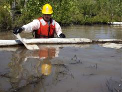 Cleanup workers use oil absorbent materials along the Yellowstone River in Laurel, Mont., on Wednesday after a pipeline ruptured last week.