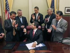 New York Gov. Andrew Cuomo, center, hands pens to legislators after signing into law a bill legalizing same-sex marriage.
