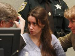 Casey Anthony talks with her attorneys Cheney Mason and Dorothy Clay Sims before the start of her sentencing hearing.