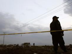A police agent guards a crime scene Friday  in Valle de Chalco, Mexico.