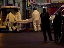 Forensic workers load a truck with bodies after gunmen stormed into a nightclub in Monterrey, Mexico, Friday.