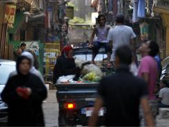Cairo residents walk through the crowded neighborhood of Mit Oqba.