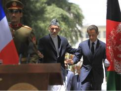 Afghan President Hamid Karzai, center, with French President Nicolas Sarkozy, says his half brother's assassination reflects the suffering of all Afghan people.
