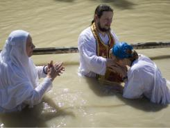 Israel has reopened daily access to the Jordan River spot where Christians believe Jesus was baptized. Here, Orthodox Christian pilgrims took part in a Holy Week baptism in April.