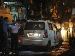 Indian security officials gather around a damaged vehicle at a bomb blast site at the Opera House area of Mumbai on Wednesday.