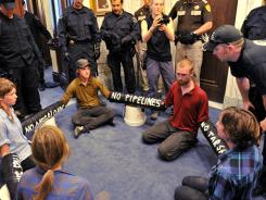 A Helena police officer talks with anti-oil protesters in the governor's office.