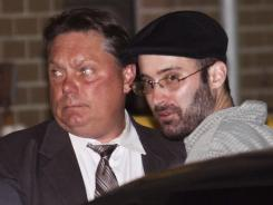 Levi Aron, right, who confessed to  killing and dismembering Leiby Kletzy, is led into a police station.