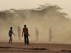 Somali boys are caught in a cloud of dust from a passing bus at Dagahaley Camp, outside Dadaab, Kenya, on Tuesday.
