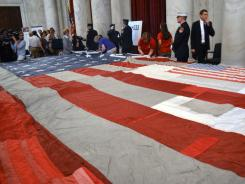 Volunteers and members of the public help restore the National 9/11 Flag on Capitol Hill in Washington on Thursday.