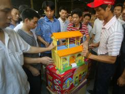 Workers display toys containing excessive lead levels at a factory in south China's Guangdong province in 2007.