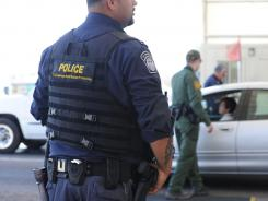 Border Patrol agents check vehicles headed north on I-19 at a checkpoint near Tubac, Ariz.