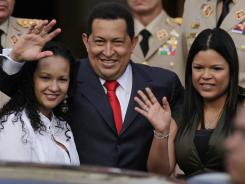 Venezuela's President Hugo Chavez, waves flanked by his daughters Rosa Virginia, right, and Gabriela, after he announced he will return to Cuba Saturday to begin a new phase of cancer treatment.