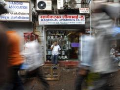 A man talks on his phone in front of a jewelry shop Friday at Zaveri Bazaar, one of the sites of Wednesday's serial blasts, in Mumbai, India.