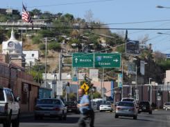 A man crosses Grand Ave. in Nogales, Ariz., near a border crossing into Mexico. The hill in the background is Mexico.