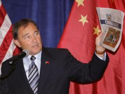 Utah Gov. Gary Herbert holds up a Chinese newspaper as he addresses the audience prior to a luncheon hosted by Herbert for the Chinese governors delegation Thursday in Salt Lake City.