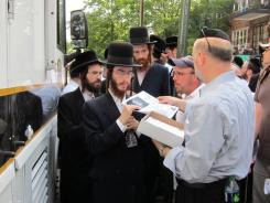 Volunteers gather at a Flatbush Shomrim Safety Patrol Mobile Command Center in the Borough Park neighborhood of Brooklyn, New York, where they are given fliers to post after 8-year-old Leiby Kletzky was reported missing the previous day.