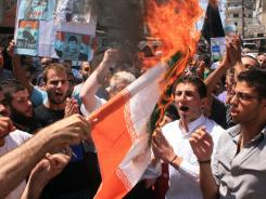 Lebanese protesters burn an Iranian flag during a rally to show solidarity with Syrian anti-government protesters in the northern city of Tripoli, Lebanon, on Friday.