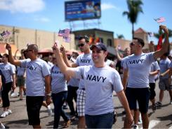 Military personnel  march along University Avenue during the San Diego gay pride parade on Saturday.