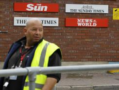 A security guard keeps watch at News International in Wapping, London, on Thursday.