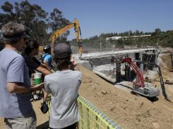 Spectators watch as construction workers take down the Mulholland Drive bridge over Interstate 405 in Los Angeles on Saturday.