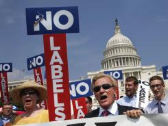 Pamela Donehower, left, and John Holman, center, rally Monday with others of the group No Labels on Capitol Hill to urge Congress and the president to find a bipartisan solution to the fiscal crisis.