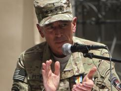 Gen. David Petraeus welcomes Gen. John Allen during a changing of command ceremony Monday in  Kabul, Afghanistan.