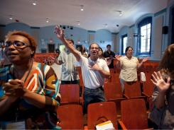 Congregants pray and sing during a service at the Forest Hills Community Church inside P.S. 144 in Queens, N.Y., where a permit is bought to use the public school for worship.